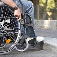 Rollstuhlfahrer im Rollstuhl an Gehsteigkante