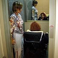 2 Frauen in engem Lift, davon eine im Rollstuhl