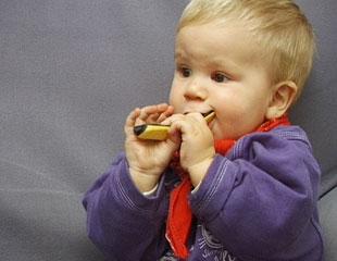 Kleinkind mit einem Plastikspielzeug im Mund