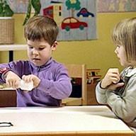 Zwei Kleinkinder versuchen, Verschlüsse von Plastikbehältern zu öffnen